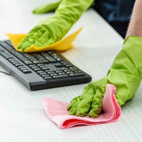 Gloved hands cleaning a table and computer keyboard