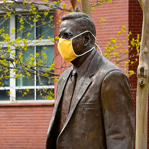 A statue of Henry Rowan wearing a face mask